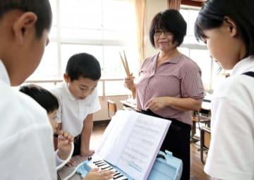 教員採用試験の合格者で最年長下別府さん。音楽大会に向けた練習など、熱心に児童を指導している=12日午後、小林市・東方小