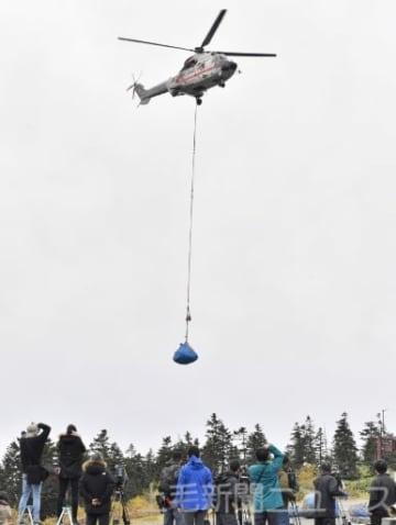 現場であらかじめ切断、梱包された機体を搬出する大型ヘリ=15日午前8時半ごろ