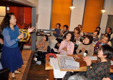 【奥田さん(左端)と一緒に歌う来場者=津市一志町波瀬の「カフェ古pos」で】