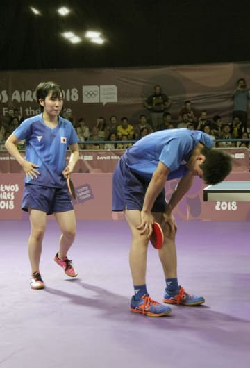 卓球混合団体決勝で中国組に敗れ、うなだれる張本(右)、平野組=ブエノスアイレス(共同)