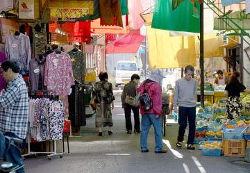 子飼商店街で買い物をする人たち。来年10月から、衣料品などの消費税率は10%に引き上げられる一方、生鮮食品などは軽減税率が適用され8%に据え置かれる=15日、熊本市中央区