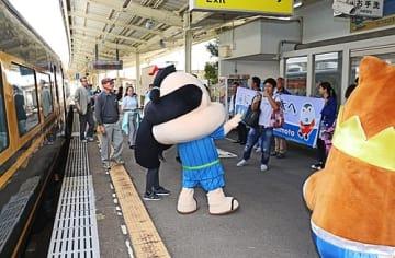 【JR串本駅でご当地キャラクターの歓迎を受ける乗客(和歌山県串本町串本で)】