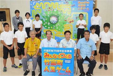 竹富町の全小学生が関わった「竹富町人生ゲーム」の巨大パネルを背に笑顔をみせる児童ら=16日、石垣市・竹富町役場