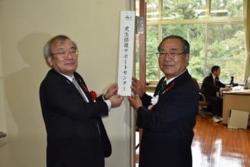 紫波地区更生保護サポートセンターの看板を掲げる新里哲之会長(右)と後藤博一所長