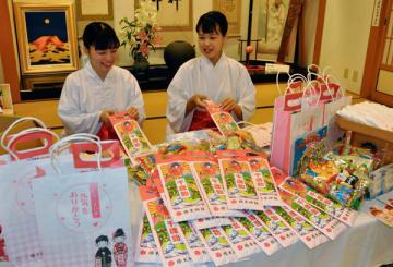 【祝い袋に千歳あめなどを詰めるみこら=鈴鹿市山本町の椿大神社で】