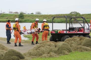 訓練で、救助者を水陸両用バギーに運ぶ隊員ら=佐賀市の嘉瀬川河川敷