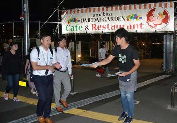 ビアガーデンに客を呼び込むアルバイト大学生(右)=大阪市北区のウメダイガーデン