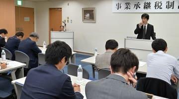 さまざまな特例処置が設けられた事業承継税制について解説する井内係長(右奥)=16日、大阪市中央区のマイドームおおさか
