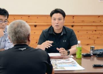 熊本地震で被災した住民に聞き取り調査をする、西原村地域おこし協力隊の吉丸和男さん(右)=西原村