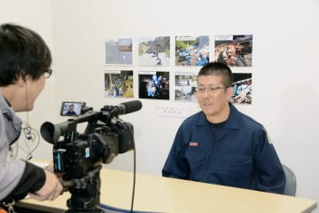 「語り部」事業の映像収録で、安否不明者捜索の経験を語る県警の本村修一警部補=16日、熊本市