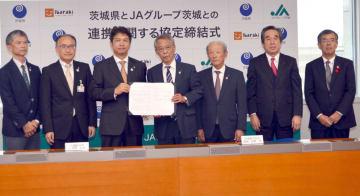 県とJAグループ茨城が初めて連携協定を締結し、協定書にサインした大井川和彦知事(左から3人目)と佐野治会長(中央)=県庁