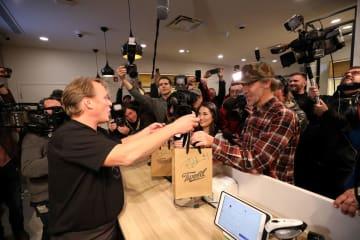 17日、カナダ東部ニューファンドランド島で、解禁された娯楽用大麻を店で受け取る客(右)(ロイター=共同)