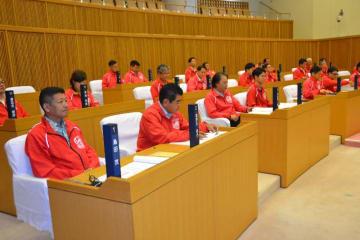 赤色のジャンパーを着て定例本会議に臨む沖縄市議=17日、沖縄市議会