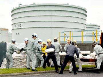 菊間国家石油備蓄基地の総合防災訓練で亀裂が入った防油堤前に土のうを積む参加者=16日午後、今治市菊間町種