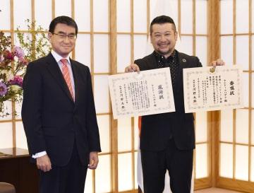 河野外相(左)から受け取った「たびレジ登録推進大使」の委嘱状などを手にするケンドーコバヤシさん=17日午前、外務省