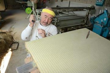 畳表を縫い付ける作業に没頭する山田豊さん=八代市