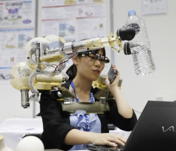 早稲田大の岩田浩康研究室が開発した「第三の腕」の実演。指示通りにペットボトルを取った=17日午後、東京都江東区の東京ビッグサイト