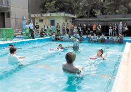 保護者らも見守る中、浮輪につかまる訓練に挑戦する児童