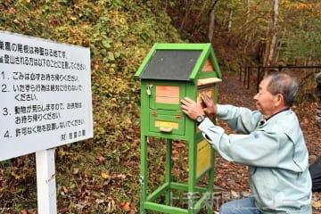 登山口にポストを設置する製作者の斎藤さん
