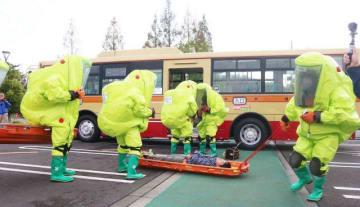車内で倒れた乗客役を搬送する消防隊員=秦野市平沢のカルチャーパーク駐車場