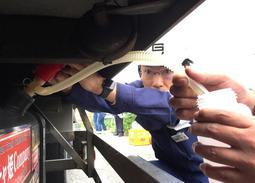 トラックから燃料を抜き取る県税事務所の職員=加東市出水