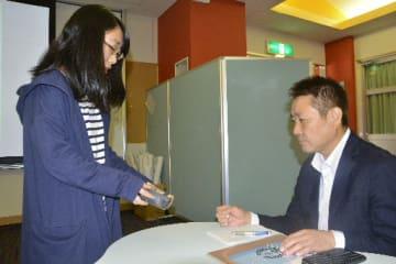 槙一郎社長(右)に新商品のパッケージについてプレゼンテーションをする学生=17日、八戸市