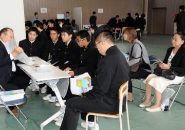 企業担当者の話に熱心に耳を傾ける生徒と保護者