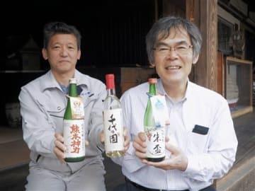 パリで売り込む純米酒「朱盃」などを手にする千代の園酒造の本田雅晴社長(右)と志垣道廣製造係長=山鹿市