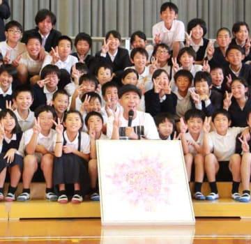 贈った絵画と一緒に児童たちと記念撮影をする木梨さん(手前中央)