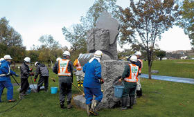 銅像を磨く高橋建設の社員たち(提供写真)