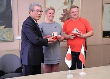 兵藤副市長(左)から歓迎のだるまを贈られるウォダルチク(中央)とカリシェフスキコーチ