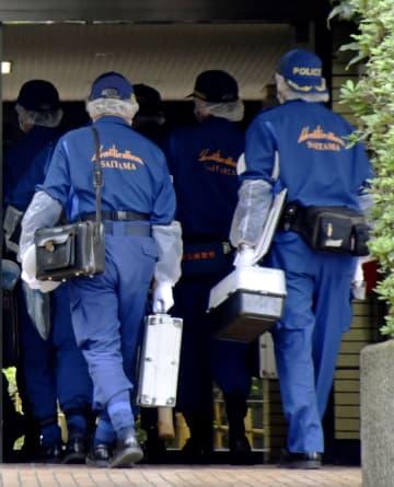 男性と妻が血を流して倒れているのが見つかったマンションに入る埼玉県警の捜査員=19日午前9時25分、埼玉県和光市