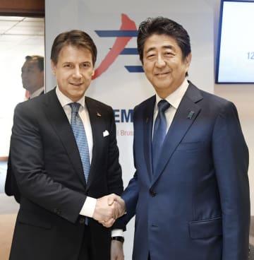 会談前に握手するイタリアのコンテ首相(左)と安倍首相=19日、ブリュッセル(共同)