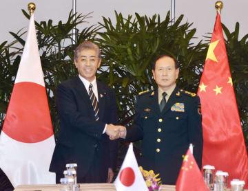 会談を前に握手する岩屋防衛相(左)と中国の魏鳳和国務委員兼国防相=19日、シンガポール(共同)