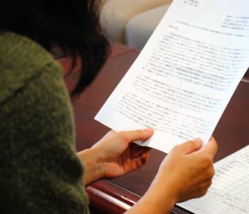 越境通園する園児も継続して保育が受けられるよう保護者一同で行政に提出した陳情書を手にする母親