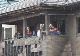実況見分で本間さん宅を調べる消防署員ら=19日午後2時40分ごろ
