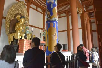 一般拝観が始まった興福寺中金堂の本尊釈迦如来坐像を見る参拝客ら=20日午前、奈良市