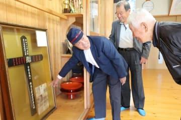 「故父の安息地」と書かれた記念碑を山田さんら住民に説明する康さん(左)=諫早市、長田町公民館