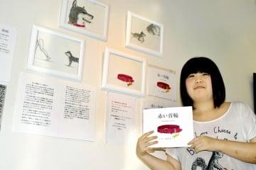 犬猫の殺処分ゼロを訴える絵本を描いた吉崎莉菜さん。原画の一部を個展で紹介している=福井県鯖江市まなべの館