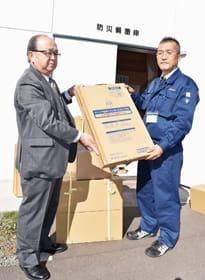 災害用トイレを寄贈する室蘭民報社の山田営業本部長(左)と受け取る宇那木課長