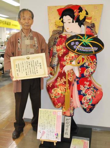 特大の羽子板を寄贈し感謝状を受け取った勝社長=18日、木更津市役所朝日庁舎