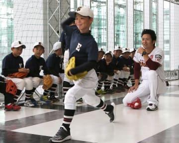 子どもに投げ方をアドバイスする牧田明久さん(右)=10月20日、福井県福井市のハピリン