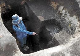 柱を建てるために掘った穴で、門柱があった場所を示す発掘調査員