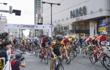「ジャパンカップサイクルロードレース」の前哨戦で、宇都宮市内の大通りを疾走する選手たち=20日午後
