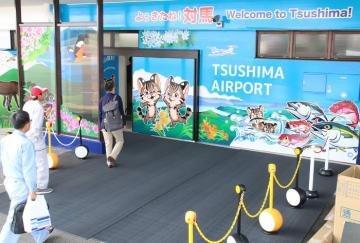 「よぅきたね! 対馬」のメッセージとともに、ツシマヤマネコや魚など対馬の自然を明るく描いた到着口=対馬空港