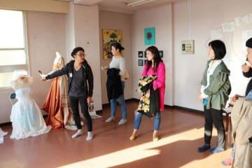 アートフェスを運営する柴田雄一郎さん(左)の案内で展示作品に見入るツアー参加者ら=逗子市逗子