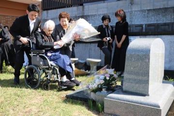 秋月さんの墓へ献花する妻すが子さん(左から2人目)=長崎市石神町