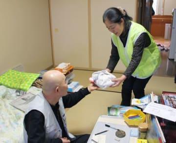 利用者に弁当を手渡す「配食ボランティア」のメンバー=弥彦村