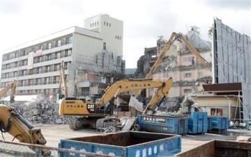 解体が進んでいる「ホテル角萬」の本館。左は営業再開後も活用予定の増築棟=19日、阿蘇市