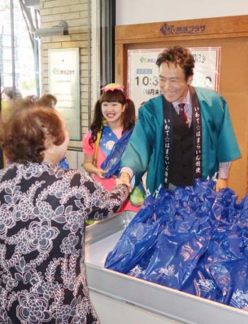 客に記念品を手渡し、握手する村上弘明さん(右)=東京都中央区